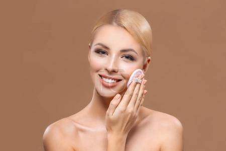 beautiful smiling woman with perfect skin applying makeup with powder puff, isolated on brown
