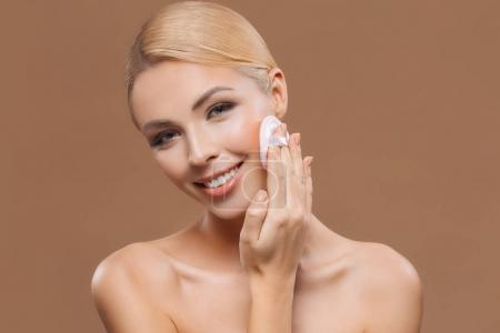 beautiful happy woman with perfect skin applying makeup with powder puff, isolated on brown