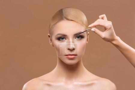 Photo for Beautiful blonde woman applying mascara, isolated on brown - Royalty Free Image