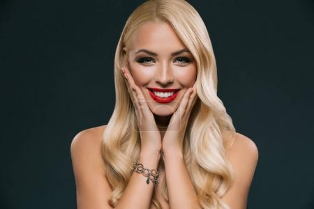 Photo for Portrait of beautiful blonde smiling woman with makeup isolated on black - Royalty Free Image