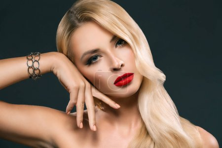 Photo for Portrait of attractive blonde woman with bracelet posing isolated on grey - Royalty Free Image