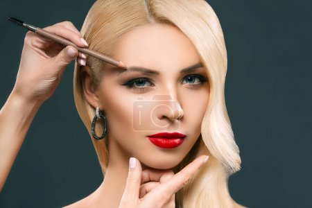 beautiful blonde woman applying eyebrow makeup, isolated on grey