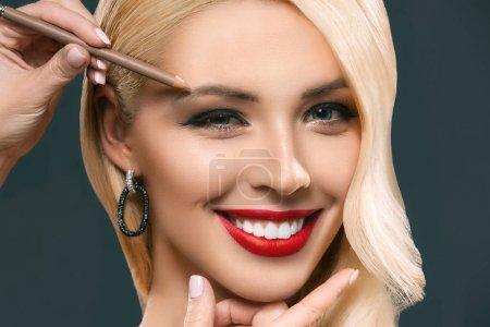 Photo pour Belle femme souriante, appliquer le maquillage des sourcils, isolé sur fond gris - image libre de droit