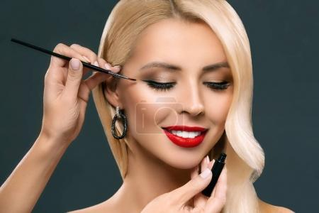 Photo for Beautiful blonde woman applying glamorous makeup with brush, isolated on grey - Royalty Free Image