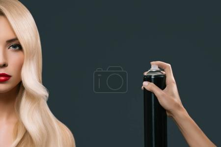 Photo pour Jeune fille blonde avec une belle coiffure à l'aide de pulvérisation, isolée sur fond gris - image libre de droit