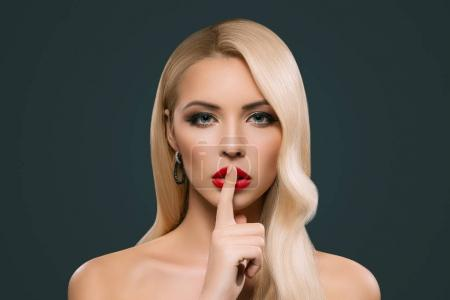 schöne sinnliche Frau mit Schweigezeichen, isoliert auf grau
