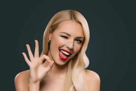 Photo for Attractive blonde winking woman showing okey sign, isolated on grey - Royalty Free Image