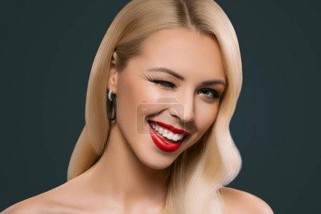 Photo for Cheerful beautiful blonde winking woman, isolated on grey - Royalty Free Image
