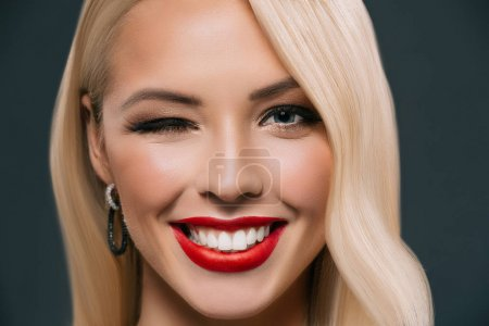 Photo for Beautiful smiling blonde woman winking isolated on grey - Royalty Free Image