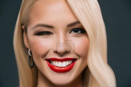 Photo pour Belle femme blonde souriante clin d'oeil isolé sur gris - image libre de droit