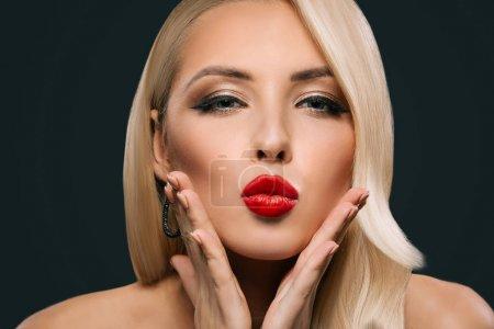 Photo pour Belle femme glamour avec maquillage et coiffure soufflant baiser, isolé sur fond gris - image libre de droit