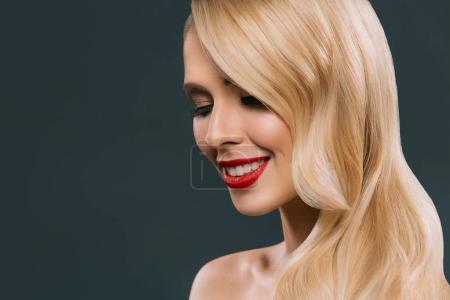 Photo pour Belle blonde femme souriante avec le maquillage, isolé sur fond gris - image libre de droit