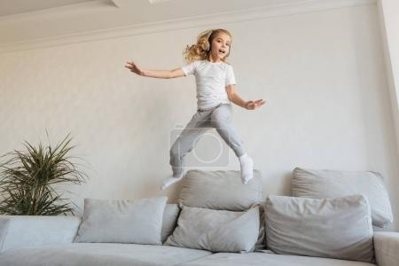 Photo for Smiling kid jumping on sofa and listening music with headphones - Royalty Free Image