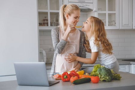smiling pregnant mother giving daughter piece of bell pepper