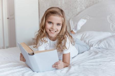 Photo for Smiling kid lying on bed with book and looking at camera - Royalty Free Image