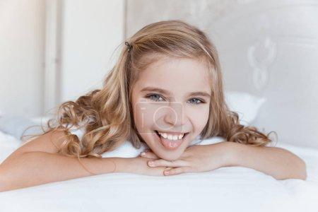 Photo pour Gamin souriant allongé sur le lit et sort la langue - image libre de droit