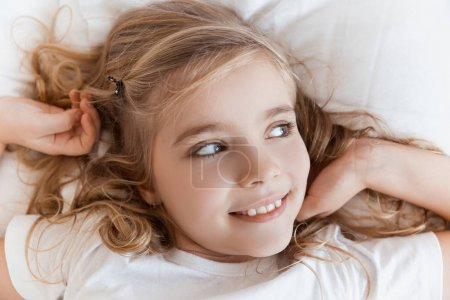 Photo for Top view of smiling adorable child lying on bed and looking away - Royalty Free Image