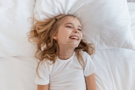 top view of smiling adorable child lying on bed
