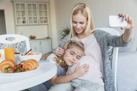 smiling pregnant mother taking selfie of sleeping daughter in kitchen