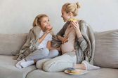 happy pregnant mother and daughter eating donuts