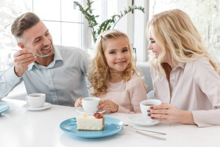 Photo for Beautiful young family spending time in cafe together on weekend - Royalty Free Image