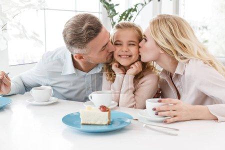 Foto de Padres besando a su hija feliz al pasar tiempo en la cafetería - Imagen libre de derechos