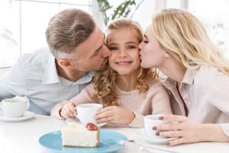 Photo for Parents kissing their daughter while spending time in cafe - Royalty Free Image