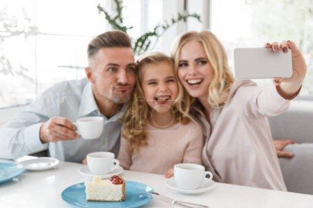Photo pour Heureux jeune famille prendre selfie et faire grimaces au restaurant - image libre de droit