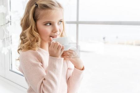 Photo for Smiling little child drinking tea and looking through window - Royalty Free Image
