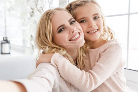 Photo for Young beautiful mother and daughter taking selfie - Royalty Free Image