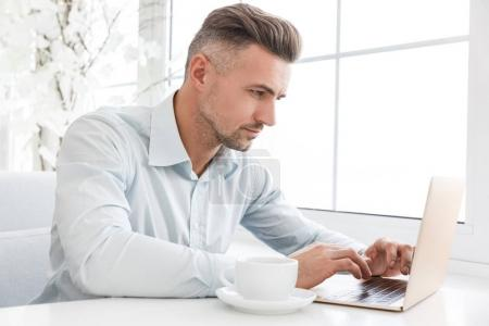 Photo for Handsome focused businessman working with laptop at cafe - Royalty Free Image