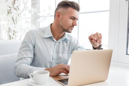 Photo pour Bel homme d'affaires regardant montre alors qu'il travaillait avec ordinateur portable au café - image libre de droit