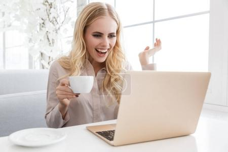 Photo for Surprised young woman working with laptop and drinking coffee in cafe - Royalty Free Image