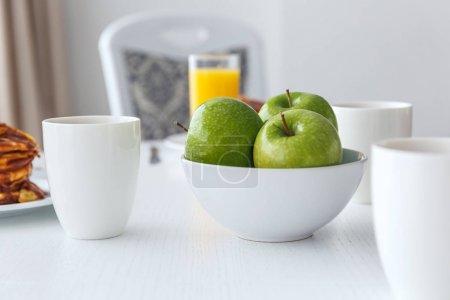 Photo pour Mugs sur tableau blanc pour le petit déjeuner et pommes vertes fraîches - image libre de droit