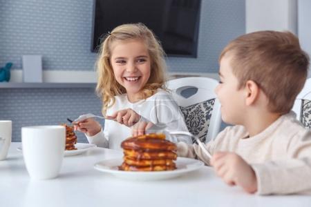 Photo pour Heureux petits enfants prendre le petit déjeuner ensemble - image libre de droit