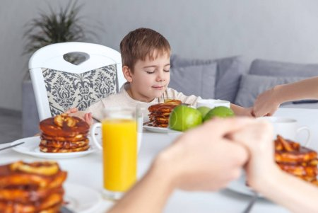 Photo for Adorable little child praying before breakfast with parents - Royalty Free Image