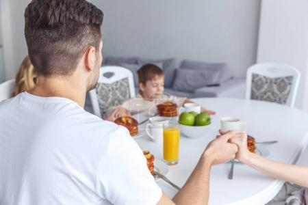 Photo for Young family praying before breakfast - Royalty Free Image