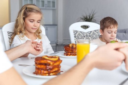 Photo for Little kids praying before breakfast with parents - Royalty Free Image