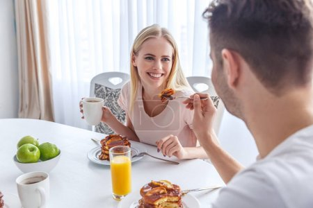 Photo for Man feeding his girlfriend on weekend breakfast - Royalty Free Image