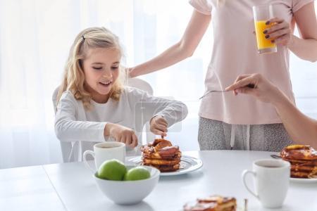 happy daughter having breakfast with her parents