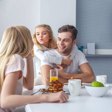 Photo for Young happy family having breakfast and having fun on weekend morning - Royalty Free Image