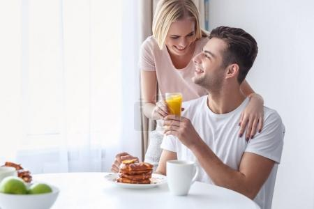 Photo for Woman passing fresh juice to her boyfriend while he taking breakfast on weekend morning - Royalty Free Image