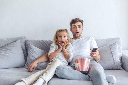 Photo pour Effrayé père et fille regarder scarry film à la maison - image libre de droit