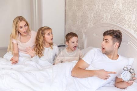 Photo for Overslept young family in bed looking at alarm clock with shocked expression - Royalty Free Image