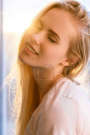 Photo pour Portrait de sensuelle jeune femme les yeux fermés avec flare coucher de soleil sur fond - image libre de droit