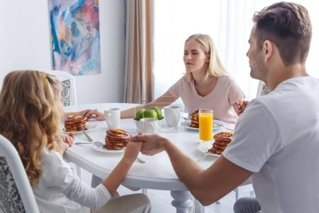 Photo for Young religious family praying before breakfast - Royalty Free Image
