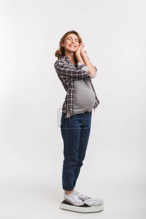 Photo for Happy young pregnant woman with closed eyes standing on scales - Royalty Free Image