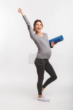 Photo for Happy young pregnant woman holding yoga mat and raising hand isolated on white - Royalty Free Image