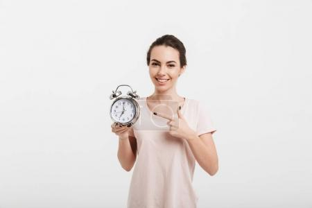smiling girl pointing on alarm clock isolated on white
