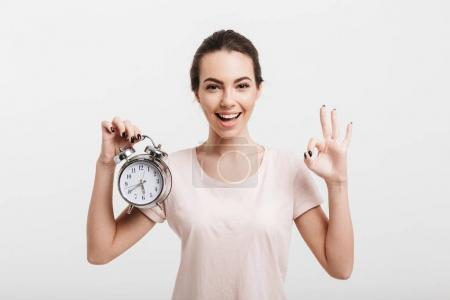 beautiful girl showing ok gesture and holding alarm clock isolated on white